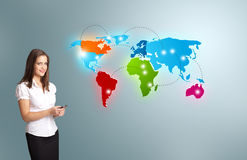 Young woman holding a phone and presenting colorful world map. Beautiful young woman holding a phone and presenting colorful world map Stock Image