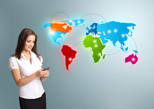 Young woman holding a phone and presenting colorful world map Stock Photo