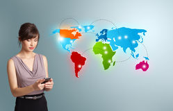 Young woman holding a phone and presenting colorful world map Stock Images
