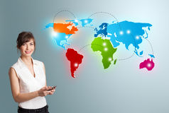 Young woman holding a phone and presenting colorful world map Royalty Free Stock Images