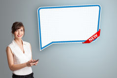 Young woman holding a phone and presenting modern speech bubble Royalty Free Stock Photo