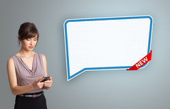 Young woman holding a phone and presenting modern speech bubble Royalty Free Stock Photography