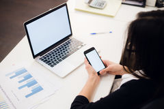Young woman holding a phone. Workplace near the window with laptop. Close up Royalty Free Stock Photos