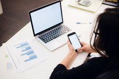 Young woman holding a phone. Workplace near the window with laptop. Close up Stock Image
