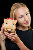 Young woman holding piggy bank. Young blonde woman holding a big piggy bank in her hands Royalty Free Stock Image