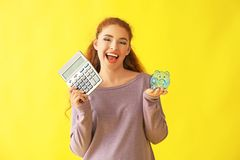 Young woman holding piggy bank and calculator on color background. Money savings concept stock photo