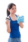 Young Woman holding piggy bank and card Royalty Free Stock Image