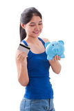 Young Woman holding piggy bank and card Stock Images