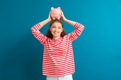 Young woman holding piggy bank on color background. Money savings concept stock photography