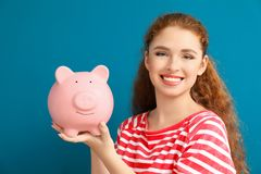 Young woman holding piggy bank on color background. Money savings concept royalty free stock photos