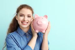Young woman holding piggy bank on color background. Money savings concept stock images