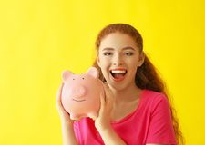 Young woman holding piggy bank on color background. Money savings concept stock photos