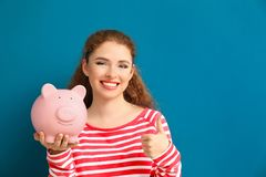 Young woman holding piggy bank on color background. Money savings concept royalty free stock images