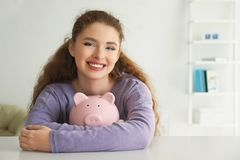 Young woman holding piggy bank indoors. Money savings concept stock photos