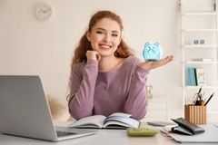 Young woman holding piggy bank indoors. Money savings concept royalty free stock images
