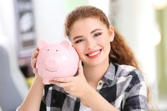 Young woman holding piggy bank indoors. Money savings concept stock images