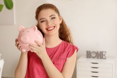 Young woman holding piggy bank indoors. Money savings concept stock image