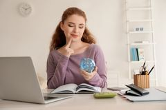 Young woman holding piggy bank indoors. Money savings concept stock photography