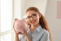 Young woman holding piggy bank indoors. Money savings concept royalty free stock photography