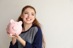 Young woman holding piggy bank near light wall. Money savings concept royalty free stock photo