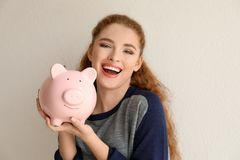Young woman holding piggy bank near light wall. Money savings concept royalty free stock image