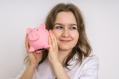 Young woman is holding piggy money bank in hands Royalty Free Stock Photo