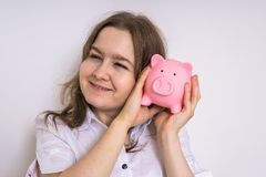 Young woman is holding piggy money bank in hands and dreaming Royalty Free Stock Photo