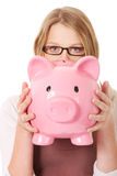 Young woman holding piggybank Stock Photos