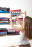 Young woman holding a pile of clothes Stock Image