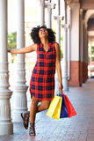 Young woman holding on pillar with colorful bags Stock Photo