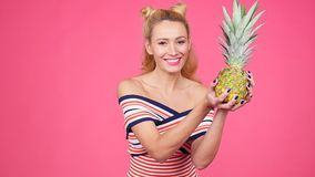 Young woman holding a pineapple on a pink background. Happy young woman in hat holding a pineapple on a pink background stock video