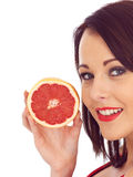 Young Woman Holding a Pink Grapefruit Royalty Free Stock Photography