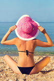 Young woman holding pink hat by the sea Royalty Free Stock Photo