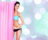 Young woman holding pink inflatable mattress Stock Photo