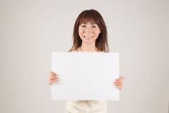 Young woman holding placard. Young woman holding a blank placard Stock Photos