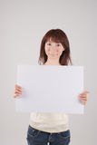 Young woman holding placard. Young Asian woman holding blank placard Stock Photo