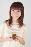 Young woman holding plant. Young Asian woman smiling with plant in hands Royalty Free Stock Photo