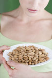 A young woman holding a plate of almonds Royalty Free Stock Photo