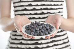 Young woman holding a plate with blueberries Stock Photography