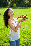 Young woman holding plate of delicious fruits Stock Image