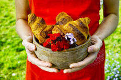 Young woman holding a plate of fresh baked croissants Royalty Free Stock Photography