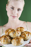 A young woman holding a plate of hot cross buns Stock Photo