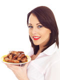 Young Woman Holding a Plate of Pork Sausages Stock Photo