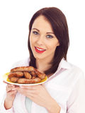 Young Woman Holding a Plate of Pork Sausages Royalty Free Stock Photos