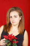 Young woman holding a Poinsettia. Portrait of a beautiful young girl wearing a black dress and holding a red Poinsettia. Studio shot over red background Stock Images