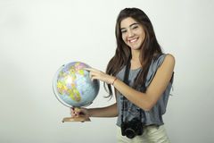Young woman holding and pointing to globe. Royalty Free Stock Photos