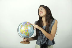 Young woman holding and pointing to globe. Stock Images