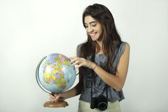 Young woman holding and pointing to globe. Royalty Free Stock Image