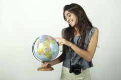 Young woman holding and pointing to globe. Royalty Free Stock Images