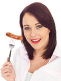 Young Woman Holding a Pork Sausage on a Fork Stock Images
